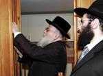 """הרב ירמיה כהן ראב""""ד פאריז קובע את המזוזה במשרדי המרכז בבריסל. לצידו,  המזכ""""ל מנחם מרגולין"""