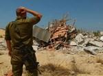 """חייל צה""""ל על רקע בית שנהרס בגוש קטיף. אחד מצילומיו המפעימים של ישראל ברדוגו"""
