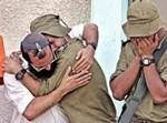 תושב הגוש וחייל מתחבקים במהלך הפינוי
