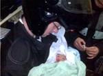 מתנדב הצלה מחזיק תינוק שיילד