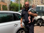 שוטר עם פעוט שחילץ מתוך רכב