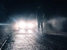 אדם על הכביש מול מכונית מתקרבת. אילוסטרציה