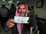 פלסטיני מציג את הכסף שקיבל מקטר