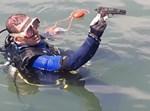 הצוללן מוציא את האקדח מהמים