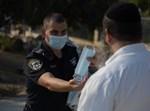 שוטר מחלק מסכה לאזרח בעיר אדומה