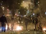 שוטרים על רקע פחים בוערים במהלך ההפגנה