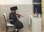 הרבי ממיאלען מנגן בכינור בהדלקה