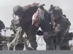 החילים מעבירים את התינוק מעבר לגדר