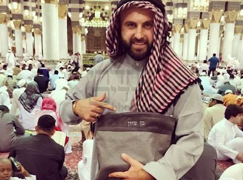 יהודי עם נרתיק תפילין על רקע מסגד מוסלמי